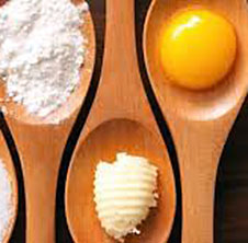 Baking spoon with egg, butter and flour